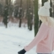 Young Pretty Blonde Girl in White Hat and Pink Sweater Walking in the Winter Forest. - VideoHive Item for Sale