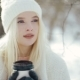 Young Attractive Blonde Girl in in Warm Clothes Standing Near the Tree with the Paper Cup - VideoHive Item for Sale