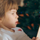 Small Girl Reading a Book in Front of Christmas Tree - VideoHive Item for Sale