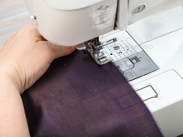 needlewoman sews strips of fabrics for patchwork - Stock Photo - Images
