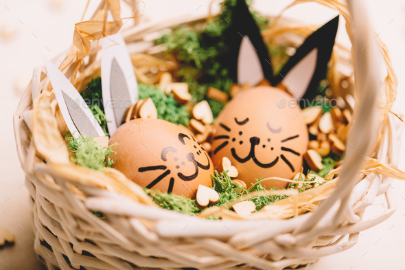 Two smiling egg-bunnies laying in the basket. - Stock Photo - Images