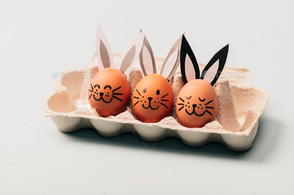 Three egg-bunnies standing in an egg carton. - Stock Photo - Images