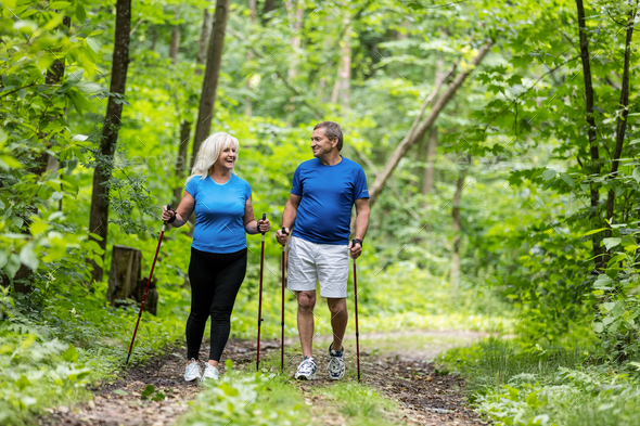 Elderly couple enjoying summer walk in the forest. - Stock Photo - Images