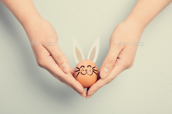 Woman's hand holding an Easter bunny - Stock Photo - Images