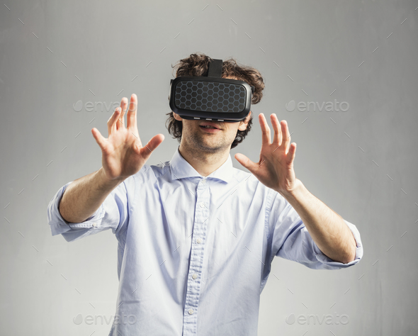Young man playing in modern VR goggles. - Stock Photo - Images