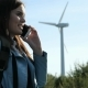 Young Woman with Cell Phone Near Clean Energy of Windmills - VideoHive Item for Sale