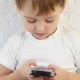 Child Boy Sitting on a White Sofa, Playing with a Smartphone, . - VideoHive Item for Sale