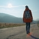 Girl with Backpack Is Going on Road Near Mountains with Beautiful Sun Glare - VideoHive Item for Sale