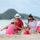 Parents with Kids Play Making Sand Castle at Tropical White Beach - VideoHive Item for Sale