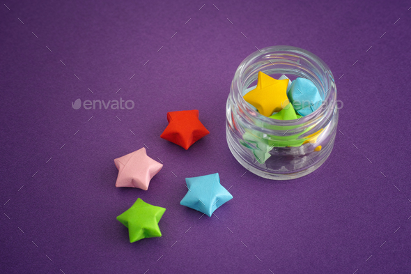 Colorful origami lucky stars spilling out of a jar - Stock Photo - Images