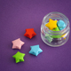 Colorful origami lucky stars spilling out of a jar - PhotoDune Item for Sale