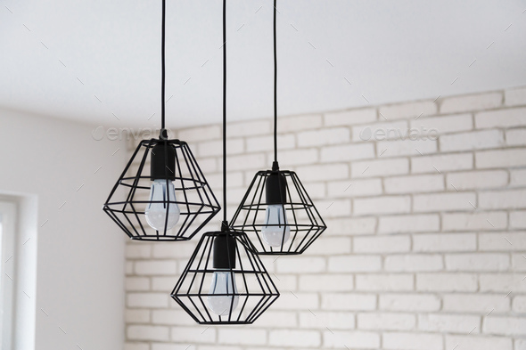 A modern loft chandelier made of black wire in a stylish white interior - Stock Photo - Images