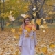 Lady In Beige Coat And Orange Scarf Turns Around And Throws Autumn Yellow Leaves - VideoHive Item for Sale