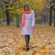 Lady In A Beige Coat And Orange Scarf Walking On Autumn Carpet Of Yellow Leaves - VideoHive Item for Sale