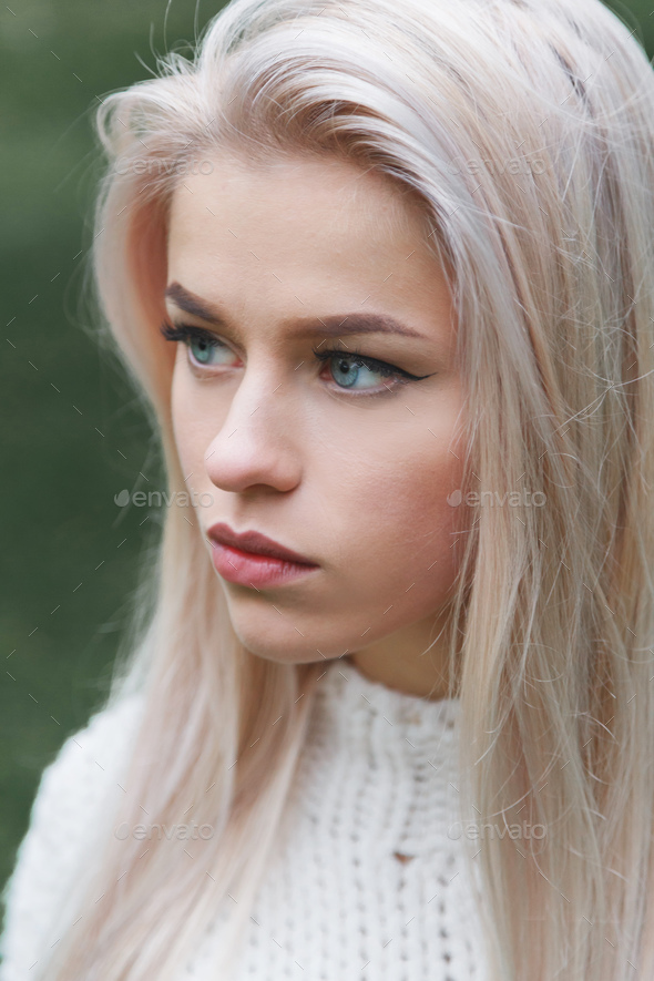 Portrait Of A Beautiful Serious Blonde Girl In A White Knitted Sweater Close-Up -4912
