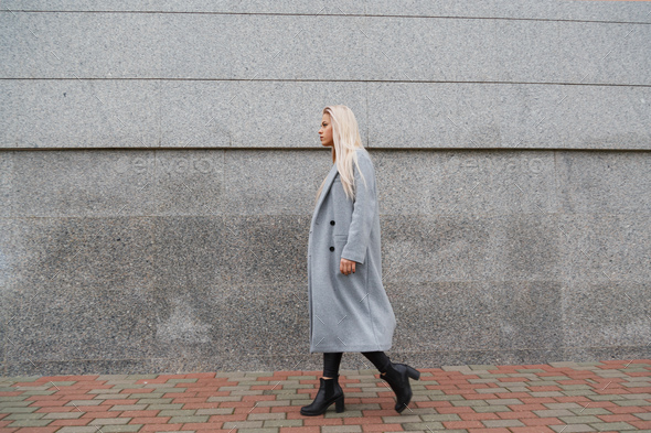 Fashion style portrait of young beautiful elegant woman in gray fur coat walking at city street - Stock Photo - Images
