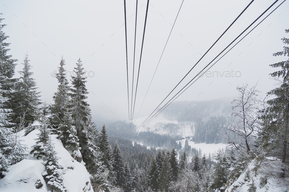 Cableway in the mountains in winter. Perspective view of the mountain woods and rope ropeway - Stock Photo - Images