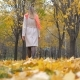 Lady In Beige Coat And Orange Scarf Walking On Autumn Carpet Of Yellow Leaves - VideoHive Item for Sale