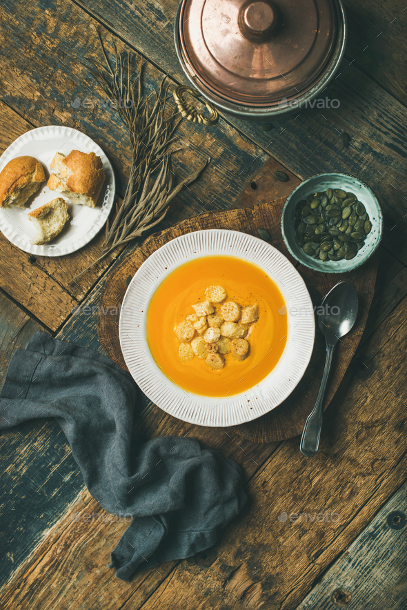 Warming pumpkin cream soup with croutons and seeds, vertical composition - Stock Photo - Images