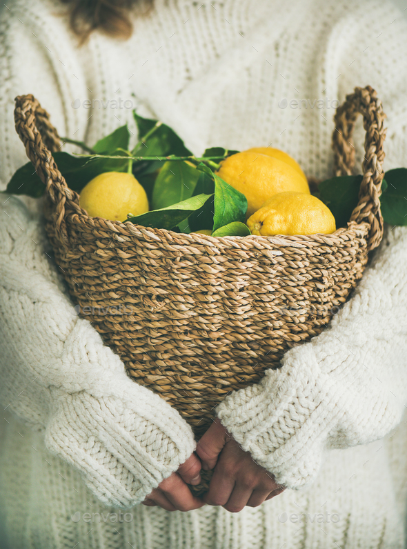 Woman in white woolen sweater holding basket of fresh lemons - Stock Photo - Images