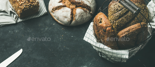 Various bread loaves on grey concrete background, copy space - Stock Photo - Images