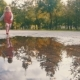 Child in Rubber Boots Running and Jumping on Puddles on a Rainy Day - VideoHive Item for Sale