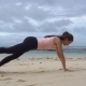 Woman Training on the Beach in Front of Sea by One Hand One Leg Plank Exercise - VideoHive Item for Sale