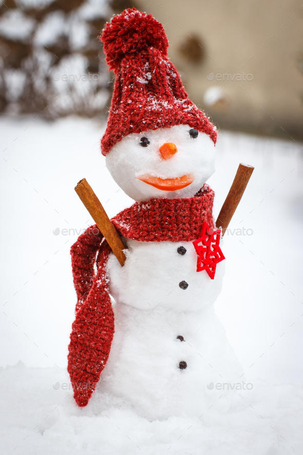Snowman with woolen scarf and cap - Stock Photo - Images