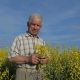 Portrait of an Elderly Farmer Stands in a Blooming Field of Yellow Flowers - VideoHive Item for Sale