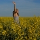 Happy Girl Running Through Field of Yellow Flowers and Waving Hands Welcoming. - VideoHive Item for Sale