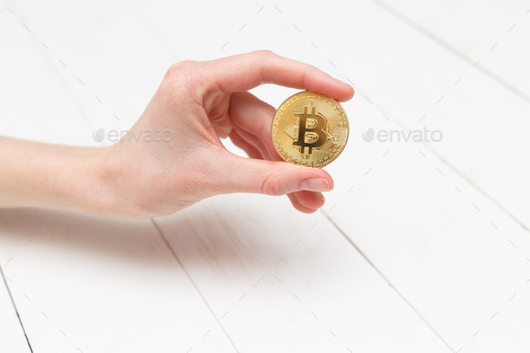Woman's hand holds a gold coin bitcoin coin. - Stock Photo - Images