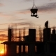 Silhouette of Construction Site Agains Sunset Sky. Warkers Wait When Crane Lifts Concrete Equipment - VideoHive Item for Sale