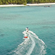 Drone Following Speedboat Towing a Water Donut with People Towards Tropical Island at High Speed - VideoHive Item for Sale