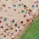 Aerial View of a Crowded Beach in a Sunny Hot Day. Yellow Sand and Umbrellas. - VideoHive Item for Sale