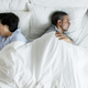 Interracial couple sleeping back to back on the bed - PhotoDune Item for Sale