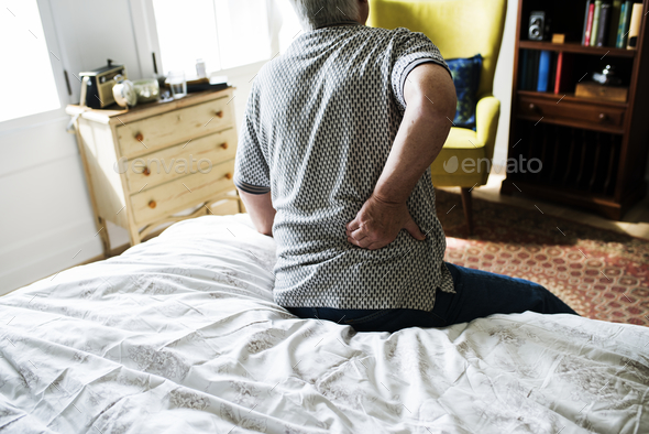 Senior man sitting on the bed in pain - Stock Photo - Images