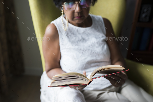 Senior woman reading book in the room - Stock Photo - Images