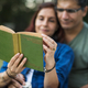 Couple spending time together reading a novel on a picnic in the jungle - PhotoDune Item for Sale