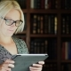 A Pretty Woman in Glasses Uses a Tablet in the Library - VideoHive Item for Sale
