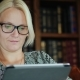 Portrait of a Woman in Glasses, Sitting in a Chair and Using a Tablet - VideoHive Item for Sale