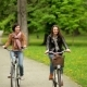 Smiling Brunettes on the Bicycles Are Riding in the Park During the Spring.Two Active Young Women - VideoHive Item for Sale