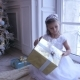 Little Adorable Girl Sitting Near the Christmas Tree and Looks at Christmas Gift - VideoHive Item for Sale