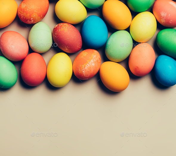 Textured colorful eggs laying on the beige background. - Stock Photo - Images
