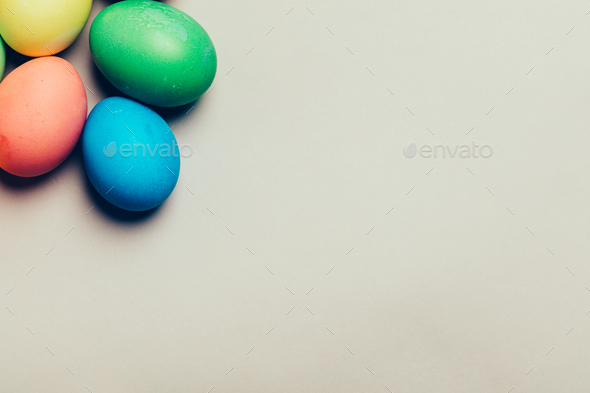 Four colored eggs in a corner on creamy background - Stock Photo - Images