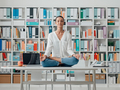 Woman practicing meditation on a desk - PhotoDune Item for Sale