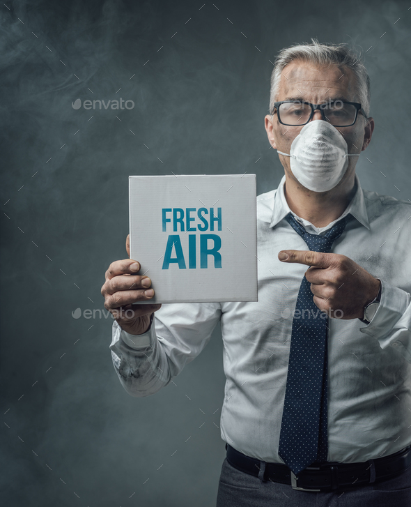 Businessman holding a sign and air pollution - Stock Photo - Images