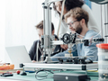 Group of students using a 3D printer and a laptop - PhotoDune Item for Sale