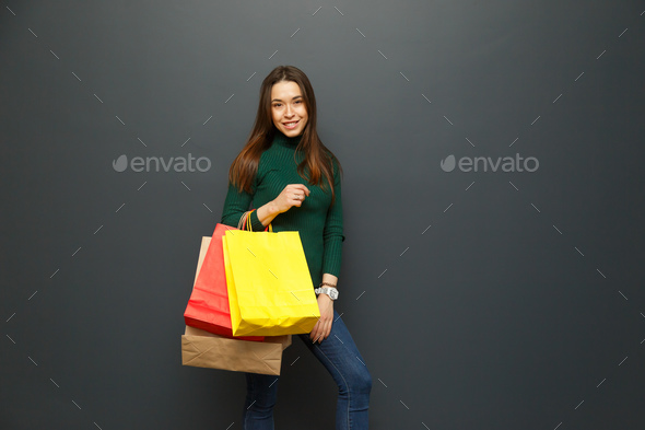 Portrait of a shopaholic girl with shopping - Stock Photo - Images