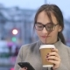 Smiling Young Female Checks Social Media on Her Smartphone While Drinking Coffee - VideoHive Item for Sale