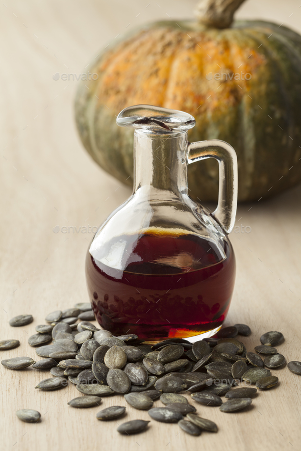 Bottle with pumpkin seed oil and roasted seeds - Stock Photo - Images